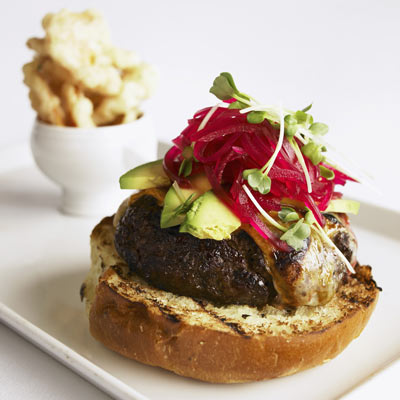 Special burger with avocado and beetroot, a very large burger with special cheese melted on a grill.