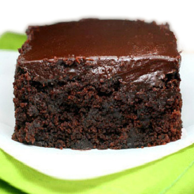 The moistest, fudgiest triple chocolate, yogurt zucchini cake you will ever have! The chocolate ganache seeps into the cracks!